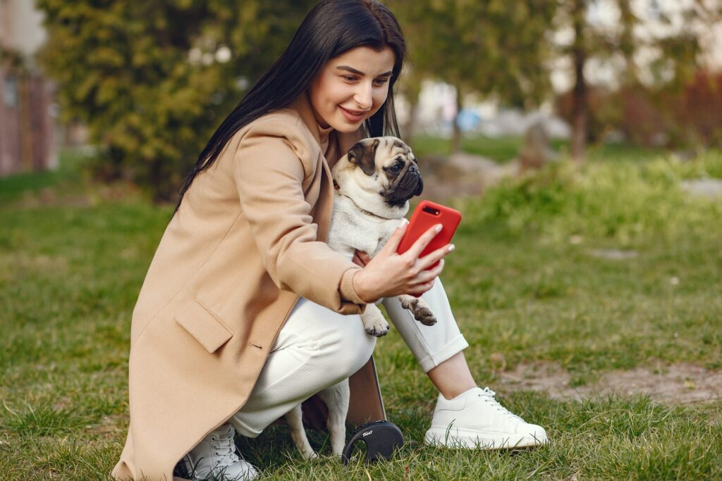 Young influencer taking a photo with her dog